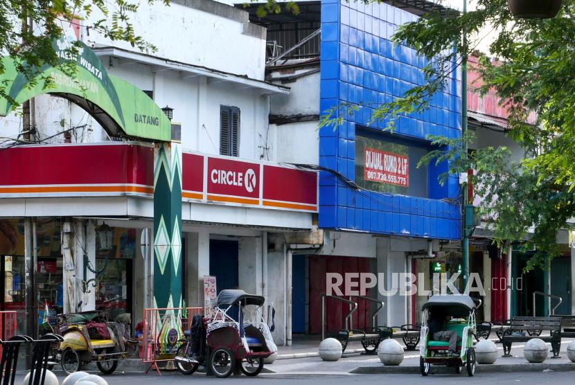 Tukang becak menunggu penumpang di kawasan wisata Malioboro, Yogyakarta, Ahad (25/7). Pengunjung ke kawasan Malioboro masih sangat sedikit, meski penyekatan masuk sudah dilonggarkan. Diketahui pada awal PPKM Darurat akses masuk kawasan Malioboro ditutup. Dan kawasan pertokoan hampir ditutup semua.