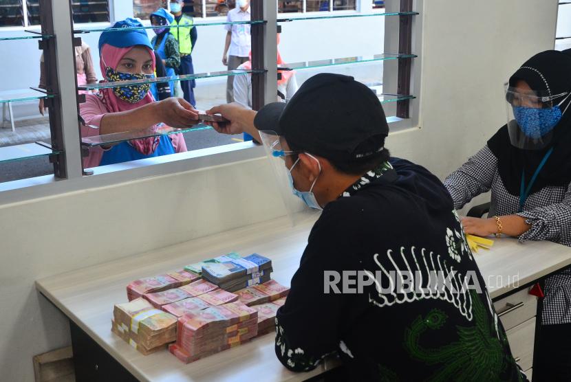 Pekerja menerima uang Tunjangan Hari Raya (THR) yang diterimanya.
