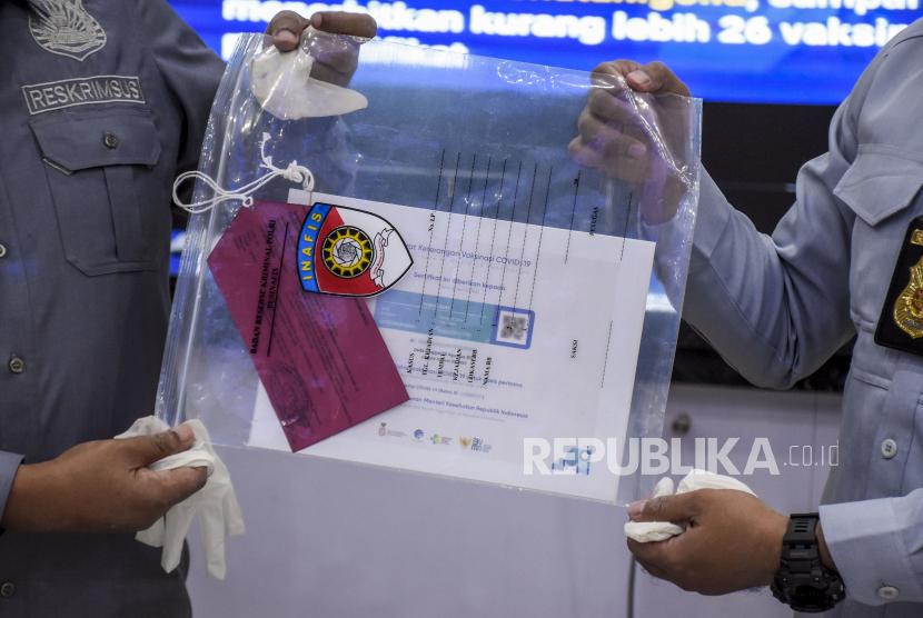 Petugas kepolisian menunjukkan barang bukti saat ekspose pengungkapan tindak pidana pembuatan sertifikat vaksinasi Covid-19 di Mapolda Jabar, Jalan Soekarno Hatta, Kota Bandung, Selasa (14/9). Dit Reskrimsus Polda Jabar berhasil mengungkap sindikat yang memperdagangkan serta menawarkan jasa pembuatan sertifikat vaksinasi Covid-19 tanpa melakukan penyuntikan dengan harga Rp100 ribu hingga Rp300 ribu per sertifikat dari empat orang tersangka, serta mengamankan barang bukti berupa laptop, ponsel dan sejumlah sertifikat vaksin Covid-19. Keempat tersangka tersebut diancam dengan hukuman 12 tahun penjara. Foto: Republika/Abdan Syakura