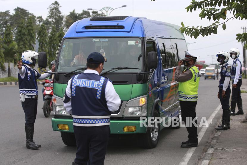 Petugas gabungan menghentikan kendaraan menjelang libur Idul Fitri untuk menekan penyebaran Covid-19 di pos pemeriksaan di pinggiran Kota Medan, Provinsi Sumatra Utara, Indonesia, 7 Mei 2021.