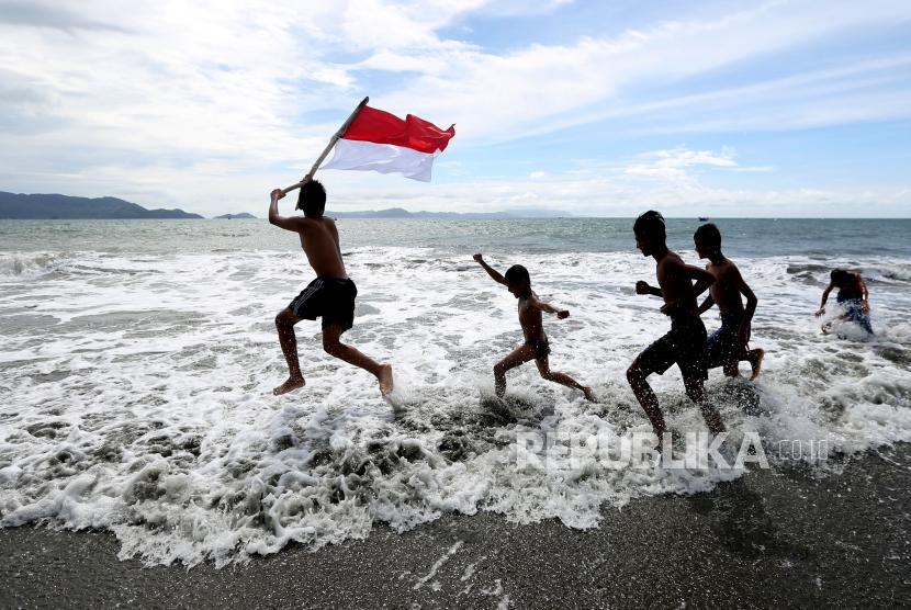 Anak-anak bermain sambil membawa bendera merah putih di pantai wisata Gampong Jawa, Banda Aceh, Aceh