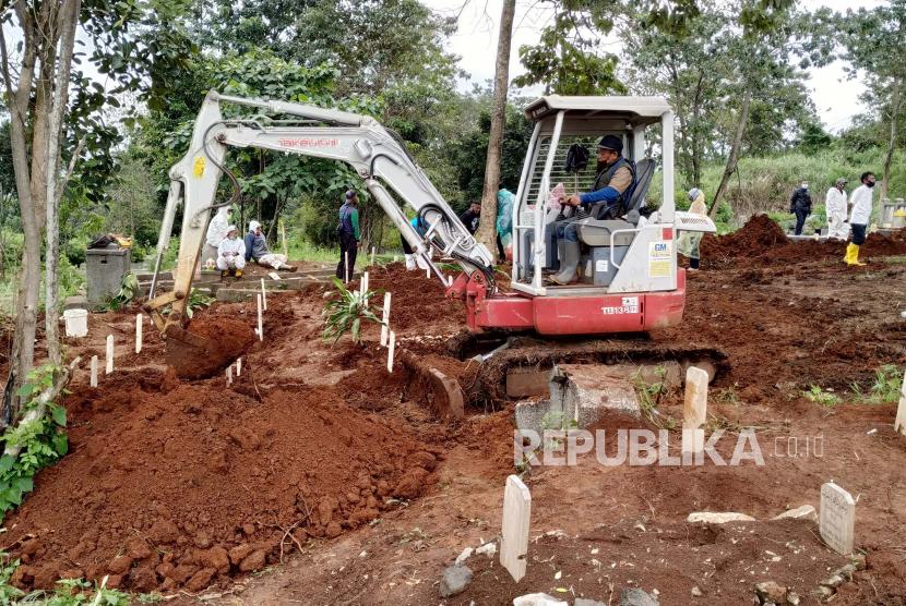 Sebuah ekskavator kecil menggali liang lahat di pemakaman khusus Covid-19 TPU Cikadut, Kota Bandung, Rabu (23/6). Melonjaknya kasus Covid-19 termasuk angka kematian akibat Covid-19 di Kota Bandung, membuat petugas pemakaman menurunkan alat berat untuk mempercepat pembuatan liang lahat.