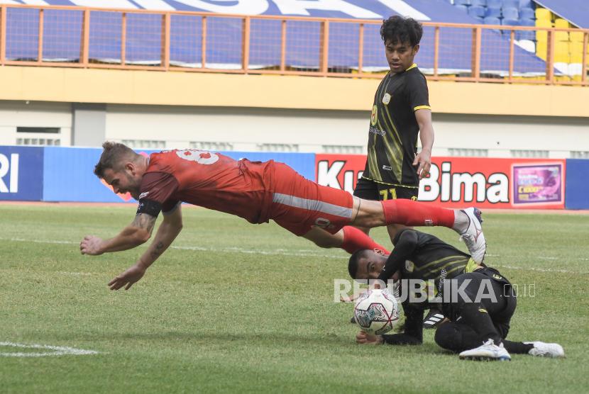 Pesepakbola PSM Makassar Wiljan Pluim (kiri) terjatuh saat berduel dengan pemain PS Barito Putera Baimatov (kanan) pada lanjutan Liga 1 di Stadion Wibawa Mukti, Kabupaten Bekasi, Jawa Barat, Senin (27/9/2021). Pertandingan berakhir dengan skor 2-0 untuk kemenangan PS Barito Putera.