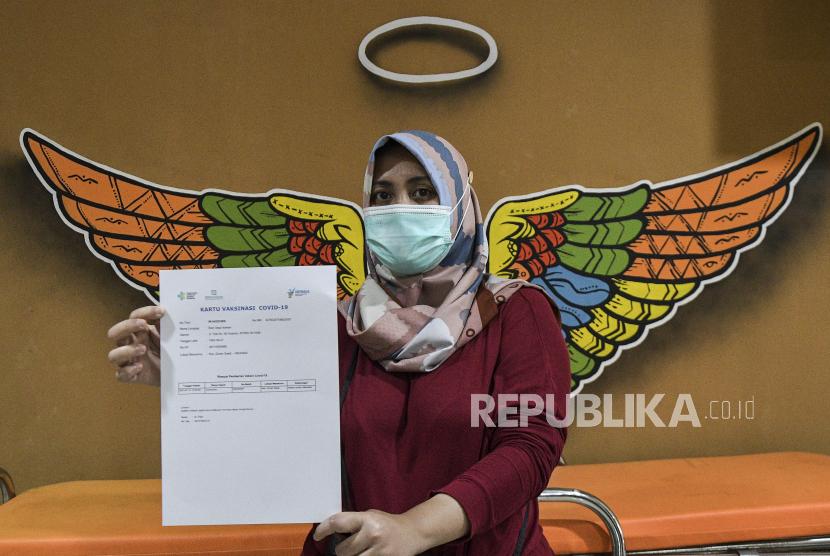 Tenaga kesehatan menunjukkan kartu vaksinasi COVID-19 seusai disuntik CoronaVac di Puskesmas Duren Sawit, Jakarta Timur, (14/1/2021). Menurut petugas sebanyak 25 tenaga kesehatan mengikuti vaksinasi COVID-19 di puskesmas Duren Sawit pada hari pertama.