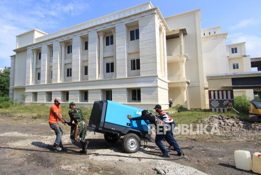 Petugas gabungan menyiapkan peralatan di gedung Asrama Haji Indramayu, Jawa Barat, Jumat (18/6/2021). Pemerintah Kabupaten Indramayu menyiapkan Asrama Haji sebagai ruang isolasi COVID-19 untuk pasien positif yang bergejala ringan dan tidak bergejala.