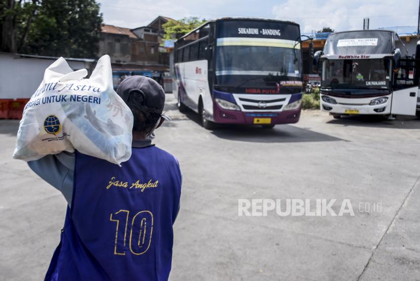 Seorang pelaku transportasi darat berjalan membawa sembako usai kegiatan pemberian bantuan sosial (Bansos). Republika