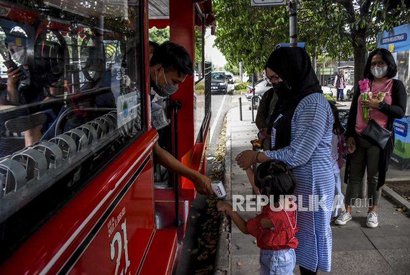 Petugas memeriksa suhu tubuh penumpang sebelum menaiki bus Bandung Tour On Bus (BANDROS) di Halte Bus Bandros di Jalan Diponegoro, Ahad (5/9). Bus wisata Bandung Tour On Bus (BANDROS) kembali beroperasi secara terbatas dengan menerapkan protokol kesehatan pencegahan Covid-19, seiring dengan menurunnya status Pemberlakuan Pembatasan Kegiatan Masyarakat (PPKM) di Kota Bandung menjadi Level 3. Foto: Republika/Abdan Syakura