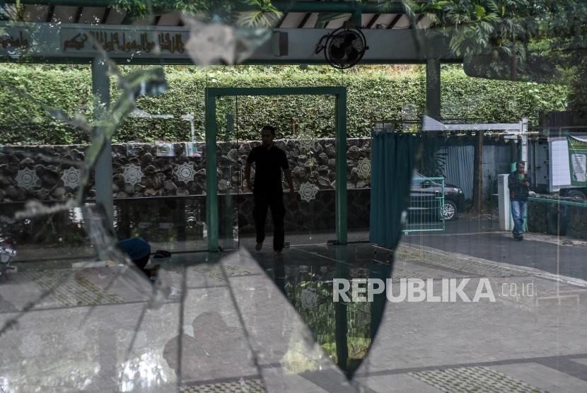 Umat muslim beraktivitas di dekat jendela yang dirusak