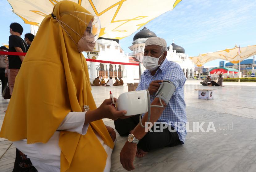 Petugas kesehatan memeriksa tensi darah warga berusia lanjut sebelum mendapatkan vaksin COVID-19 pada vaksinasi merdeka di halaman masjid raya Baiturrahman, Banda Aceh, Aceh, Senin (6/9/2021). Vaksinasi merdeka yang digelar secara serentak pada 6-7 September 2021 di seluruh Indonesia merupakan program sinergi staf khusus Presiden bersama Kapolri dan  Panglima TNI untuk membantu pemerintah memutuskan mata rantai penyebaran serta penularan COVID-19.