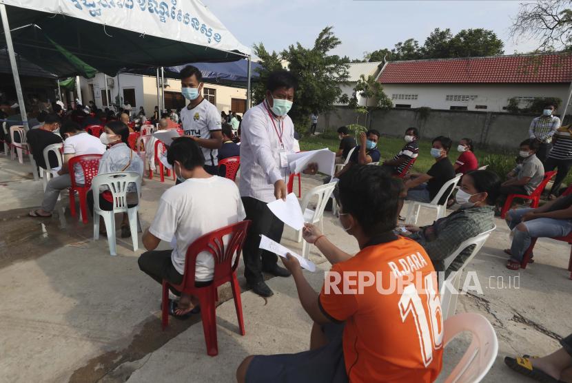Anggota staf membagikan formulir kepada penduduk desa sebelum dosis kedua mereka di lokasi vaksin COVID-19 Sinopharm, di luar Phnom Penh, Kamboja, Rabu, 28 April 2021.