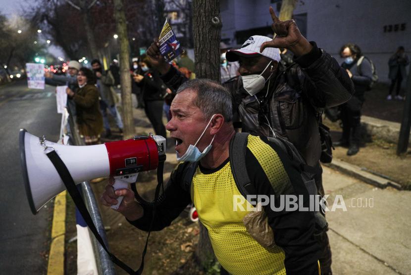 Warga Kuba yang tinggal di Chili meneriakkan slogan-slogan menentang pemerintah Kuba selama protes di luar Kedutaan Besar Kuba di Santiago, Chili, Rabu, 14 Juli 2021. Protes itu terjadi setelah protes akhir pekan yang jarang terjadi terhadap rezim komunis di negara pulau itu