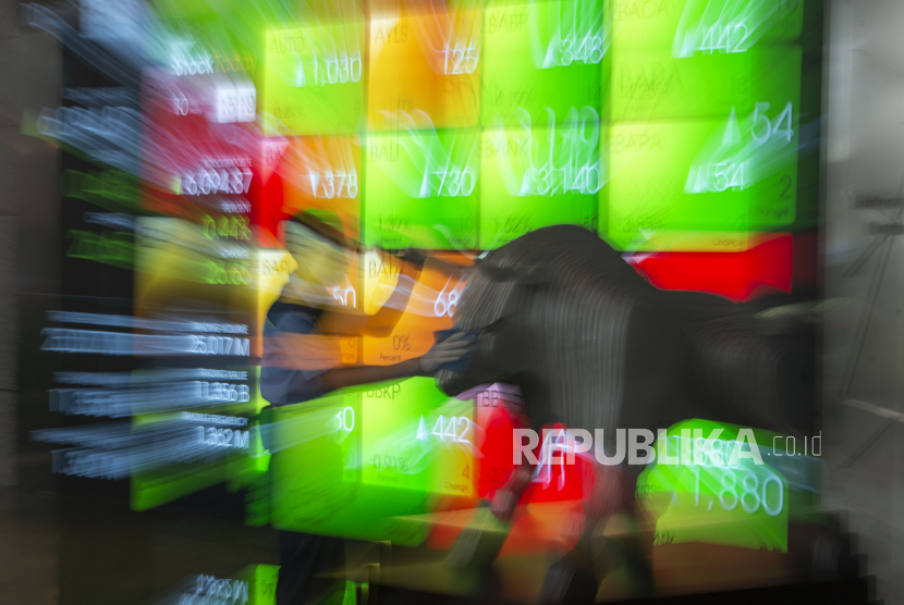 Pekerja membersihkan patung banteng dengan latar belakang layar pergerakan Indeks Harga Saham Gabungan (IHSG). IHSG berpeluang menguat seiring kepastian tapering off oleh The Fed.