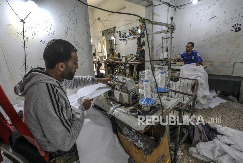 Israel Izinkan Ekspor dari Gaza. Warga Palestina memproduksi pakaian pelindung di sebuah pabrik jahit kecil di Kota Gaza,  Senin (30/3). Beberapa pabrik pakaian di Jalur Gaza telah mengubah jalur produksinya untuk memproduksi peralatan pelindung seperti pakaian pelindung dan masker wajah medis untuk pasar Israel dan Tepi Barat di tengah kekhawatiran tentang penyebaran pandemic penyakit COVID-19 yang disebabkan oleh SARS CoV-2 virus Corona