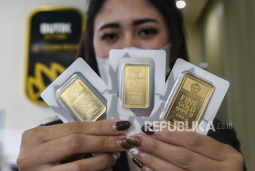 Karyawan menunjukan emas batangan di Butik Emas Antam, Kebon Sirih, Jakarta (ilustrasi)