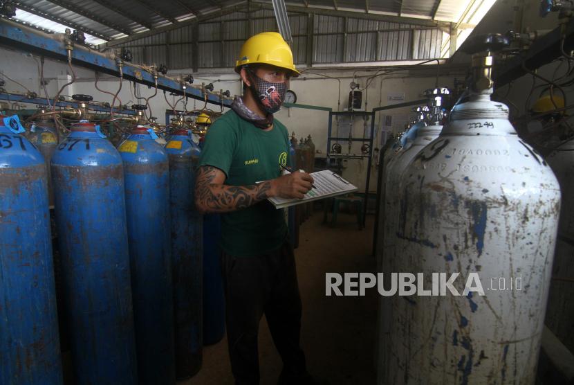 Seorang pekerja mencatat nomor seri tabung oksigen yang telah diisi di pabrik oksigen.