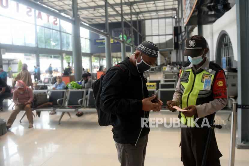 Petugas memeriksa tiket calon penumpang kereta jarak jauh di Stasiun Senen, Jakarta, Ahad (18/4).