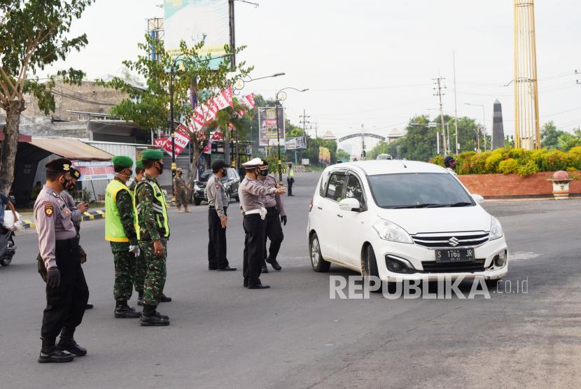 Petugas gabungan menghentikan mobil berplat nomor luar daerah saat penyekatan dalam rangka larangan mudik di Kota Madiun, Jawa Timur, Selasa (4/5/2021). Penyekatan yang dilakukan petugas gabungan TNI, Polri, Satpol PP dan Badan Penanggulanan Bencana Daerah (BPBD) itu dimaksudkan untuk mengantisipasi pemudik masuk wilayah Kota Madiun guna mencegah penularan COVID-19.