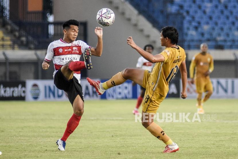 Gelandang Bhayangkara FC Adam Alis Setyani (kanan) berebut bola dengan pemain Madura United dalam pertandingan lanjutan BRI Liga 1-2021/2022 di Stadion Si Jalak Harupat, Kabupaten Bandung, Sabtu (18/9). Dalam pertandingan tersebut Bhayangkara FC mengalahkan Madura United dengan Skor 1-0.