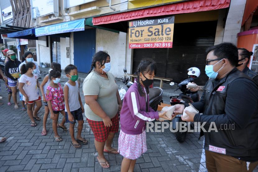 Warga membagikan nasi bungkus gratis kepada yang membutuhkan di kawasan Kuta, Badung, Bali, Rabu (28/7/2021). Aksi berbagi ratusan nasi bungkus secara gratis tersebut dilakukan sebagai bentuk solidaritas antar warga untuk meringankan beban masyarakat yang membutuhkan khususnya di kawasan wisata Kuta yang perekonomiannya terdampak pandemi COVID-19.