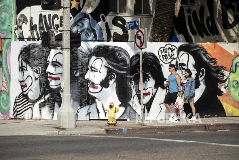 Sepasang kekasih berjalan melewati mural di Main Street, saat California mencabut sebagian besar pembatasan yang diberlakukan sebagai tanggapan terhadap pandemi COVID-19, di Venice Beach, California, AS, 15 Juni 2021.
