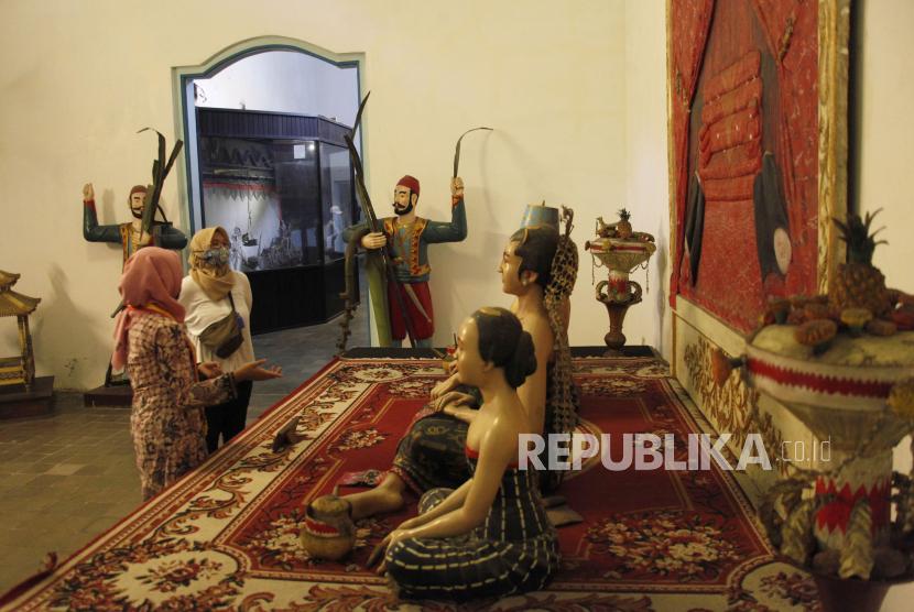 Pengunjung mengamati koleksi museum Keraton Kasunanan Surakarta Hadiningrat saat pembukaan kembali museum setempat, Solo, Jawa Tengah, Ahad (8/11/2020). Museum Keraton Kasunanan Surakarta Hadiningrat Solo mulai dibuka kembali untuk umum dengan menerapkan protokol kesehatan bagi pengunjung.