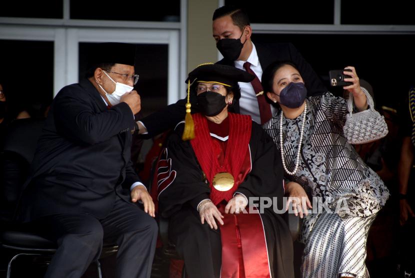 Presiden Indonesia ke-5 Prof. Dr. (H.C) Megawati Soekarnoputri (tengah) berswafoto  bersama Ketua DPR Puan Maharani (kanan) dan Menteri Pertahanan Prabowo Soebianto (kiri)  seusai prosesi  Pengukuhan Guru Besar,  di Aula Merah Putih, Universitas Pertahanan, Sentul, Kabupaten Bogor, Jawa Barat, Jumat (11/6/2021). Megawati Soekarnoputri menerima gelar profesor kehormatan (guru besar tidak tetap) Ilmu Pertahanan Bidang Kepemimpinan Strategik pada Fakultas Strategi Pertahanan Universitas Pertahanan.
