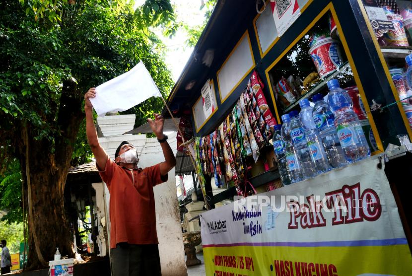 Pedagang memasang bendera putih tanda berkabung pada gerobak,l di kawasan Malioboro, Yogyakarta, Jumat (30/7). Pemasangan bendera putih ini sebagai tanda simbolis Malioboro Berkabung oleh Paguyuban Kawasan Malioboro. Hal ini imbas ditutupnya kawasan Malioboro selama pemberlakuan PPKM Darurat. Sehingga pedagang kaki lima sama sekali tidak ada pemasukan selama itu. Mereka meminta pelonggaran masuk ke Malioboro bagi pengunjung. Serta meminta kebijakan yang serta terobosan yang nyata berdampak bagi mereka.