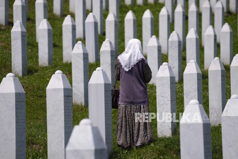 Seorang wanita berjalan berdiri di antara kuburan korban pembantaian Srebrenica, di pemakaman peringatan di Potocari, dekat Srebrenica, Bosnia timur, Selasa, 8 Juni 2021.