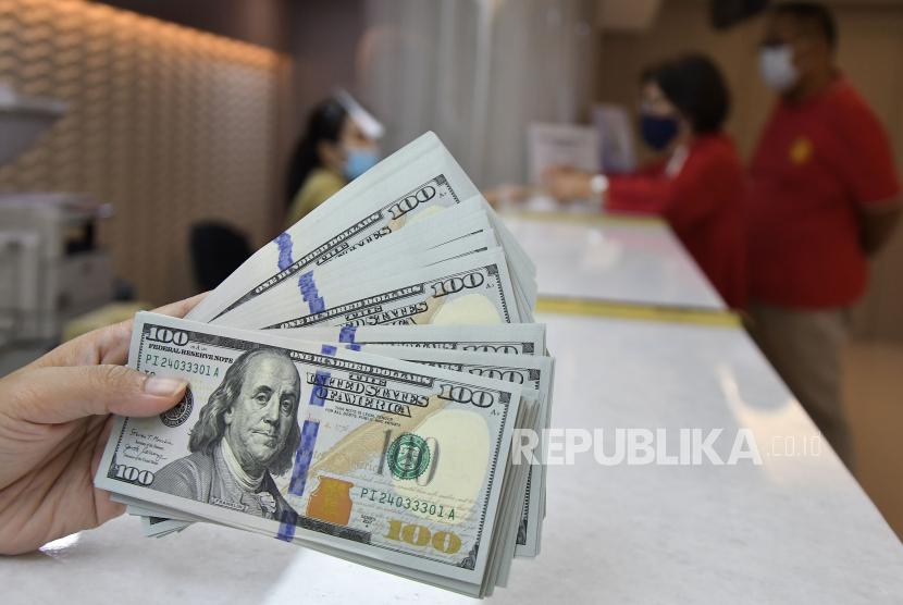 Karyawan menunjukkan uang dolar Amerika Serikat (AS) di tempat penukaran valuta asing, Jakarta, Rabu (6/1). Dolar AS menguat untuk sesi kedua berturut-turut pada akhir perdagangan Senin (27/9), didukung oleh kenaikan imbal hasil obligasi pemerintah AS.