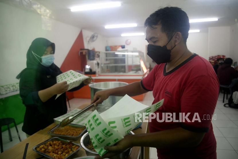 Penjual membungkus makanan untuk dibagikan kepada warga yang membutuhkan di Rumah Makan Wartegan, (Prayogi/Republika)