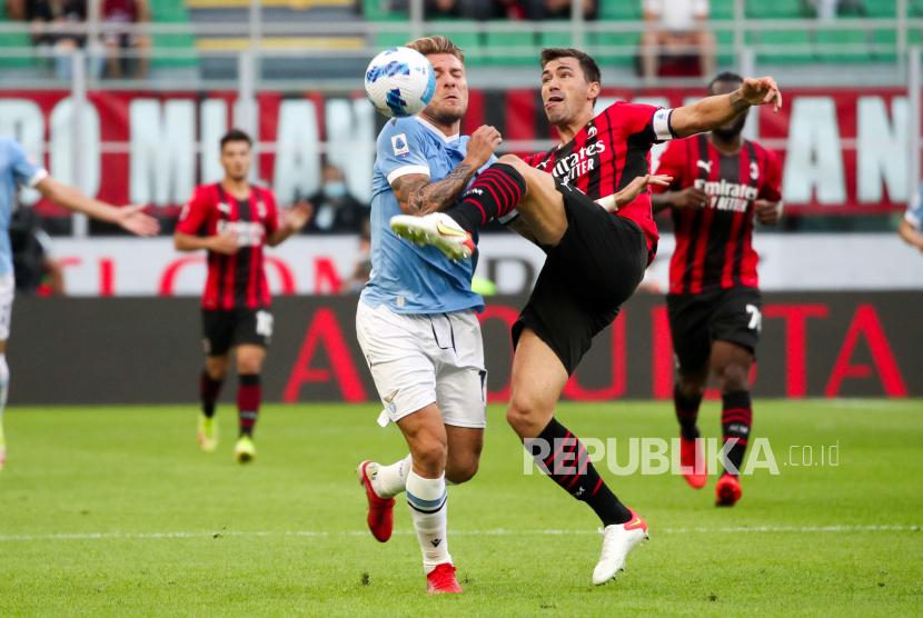 Bek AC Milan Alessio Romagnoli (kanan) dan penyerang Lazio Ciro Immobile beraksi pada pertandingan sepak bola Serie A Italia AC Milan vs SS Lazio di Stadion Giuseppe Meazza di Milan, Italia, Ahad (12/9).