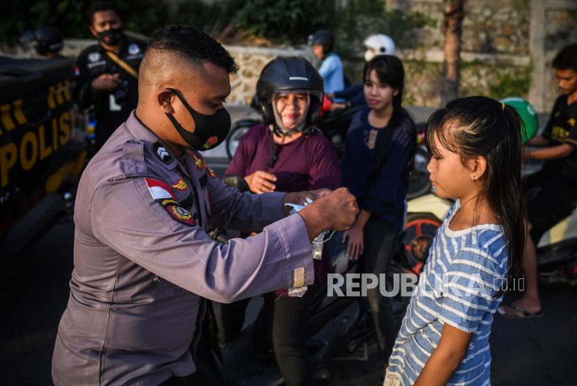 Petugas kepolisian memakaikan masker ke pengendara untuk menekan penularan COVID-19.