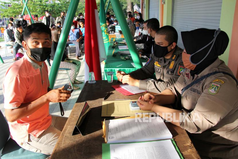 Petugas mendata seorang warga yang melanggar protokol kesehatan (prokes)