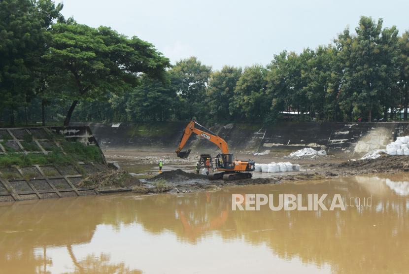 Pekerja menggunakan alat berat untuk mengeruk sedimen di kawasan Dam Jati Sungai Madiun di Magetan, Jawa Timur, Senin (22/2/2021). Pengerukan tersebut dimaksudkan untuk mengurangi risiko bencana banjir akibat terjadinya sedimentasi di Sungai Madiun.