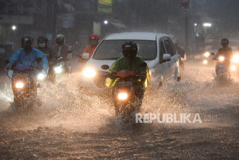 Pengendara melintasi genangan air yang menutupi ruas jalan di kawasan Mampang Prapatan, Jakarta, Ahad (19/9).  Genangan setinggi 20 sampai 30 centimeter tersebut terjadi sekitar pukul 17.30 WIB akibat curah hujan yang tinggi dan sistem drainase yang buruk. Republika/Thoudy Badai