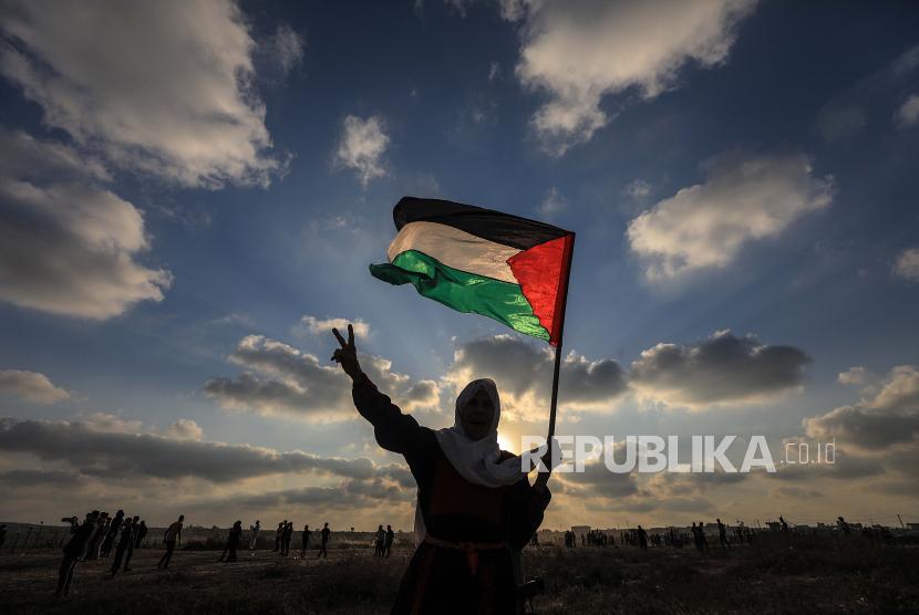 Warga Gaza mengangkat bendera Palestina. Pemerintah Palestina (PA) berencana mengadakan pemilihan kepala daerah (pilkada) pada Desember.
