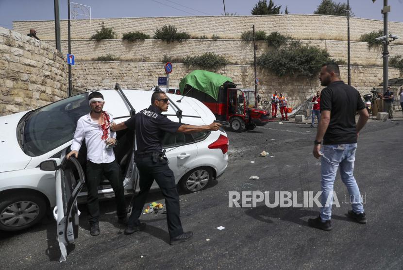 PM Skotlandia Kecam Serangan Israel di Al Aqsa. Foto: Seorang petugas polisi Israel melindungi seorang pengemudi Yahudi yang diserang oleh pengunjuk rasa Palestina di dekat Kota Tua Yerusalem, Senin 10 Mei 2021.