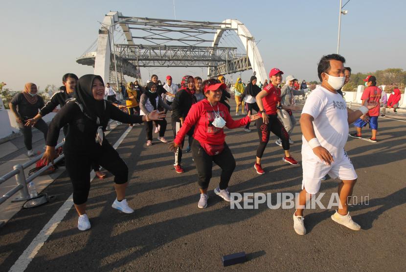 Warga berolahraga di kawasan Jembatan Suroboyo, Surabaya, Jawa Timur, Ahad (1/8/2021). Meskipun di tengah pandemi COVID-19, Jembatan Suroboyo yang merupakan salah satu ikon kota Surabaya berlokasi di kawasan Kenjeran tersebut ramai dikunjungi warga  untuk berolahraga, bersepeda ataupun sekedar menikmati pemandangan pantai.