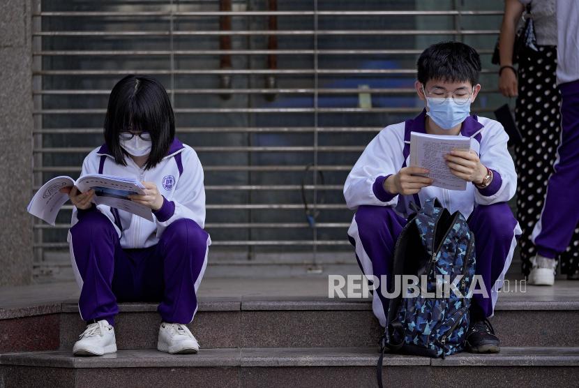 Siswa mengenakan masker wajah untuk membantu mengekang penyebaran virus corona meninjau buku teks di luar sekolah sebelum ujian masuk perguruan tinggi nasional China, yang dikenal sebagai gaokao, di Beijing, Senin, 7 Juni 2021.