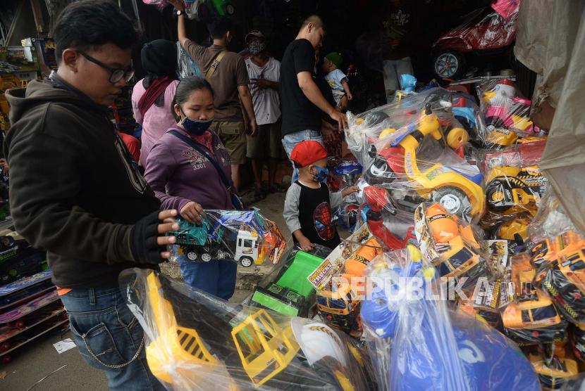 Seorang anak bersama orang tuanya memilih mainan yang dijual di Pasar Gembrong, Jakarta. ilustrasi