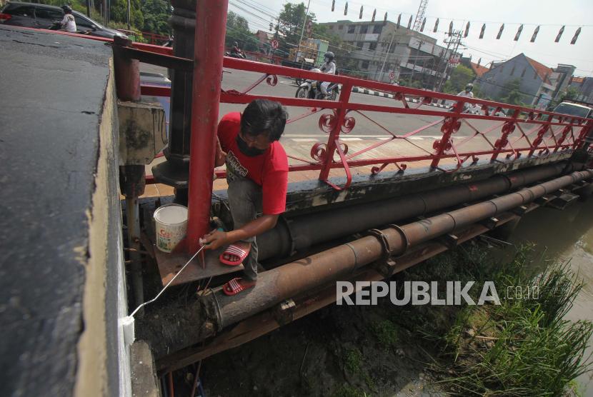 Pekerja mengecat Jembatan Merah, di Surabaya, Jawa Timur, Senin (15/3/2021). Pengecatan bangunan cagar budaya yang dibangun pada tahun 1809 tersebut agar tetap terawat.