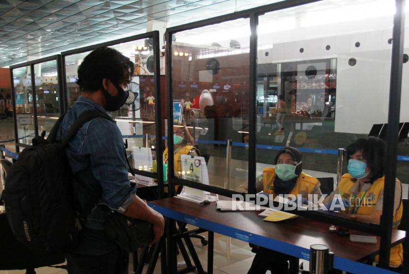 Petugas memeriksa dokumen kesehatan calon penumpang sebelum melakukan lapor diri (chek in) di Terminal 3 Bandara Soekarno Hatta, Tangerang, Banten, Senin (8/6/2020). PT Angkasa Pura II selaku pengelola bandara mulai menjalankan skenario protokol penerapan tatanan normal baru mulai dari pemeriksaan kesehatan, penggunaan fasilitas bandara, tramsaksi tanpa uang cash disejumlah tenant bisnis yang ada di bandara, serta menerapkan prosedur physical distancing
