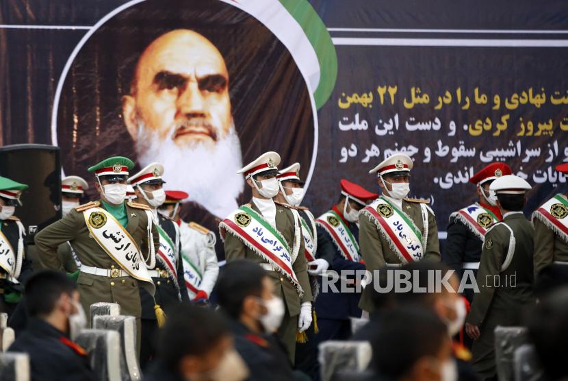 Tentara Iran berdiri di samping foto besar mendiang pendiri Iran dari Republik Islam, Ayatollah Ruhollah Khomeini dalam sebuah upacara dalam rangka peringatan 42 tahun kembalinya Khomeini dari pengasingan dari Paris, di makamnya di Teheran selatan, Iran, Ahad (31/1/2021).