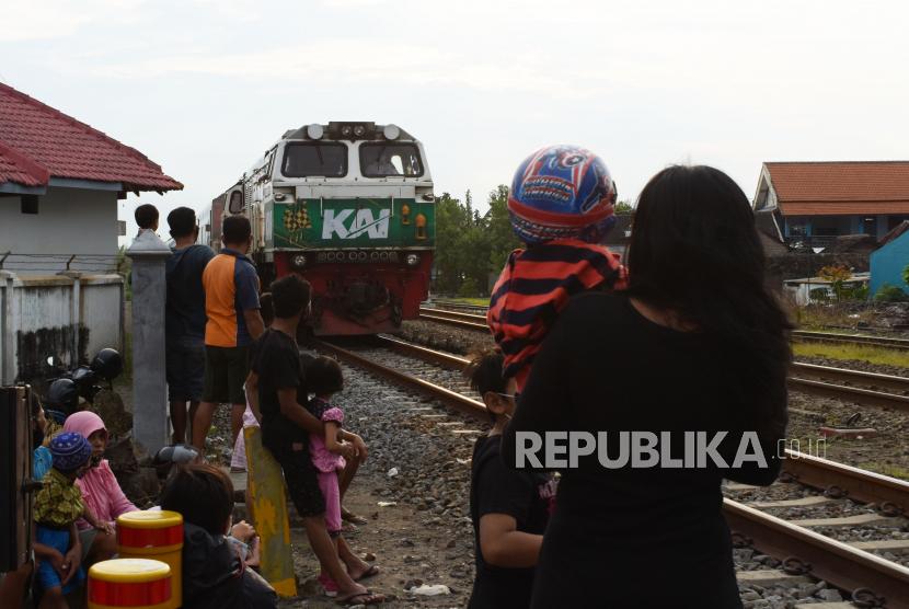 Warga melihat kereta api melintas di kawasan Stasiun KA Madiun, Jawa Timur, Ahad (18/4/2021). Kawasan stasiun dan jalur perlintasan kereta api seringkali dijadikan sebagai lokasi untuk menanti berbuka puasa atau ngabuburit oleh warga meskipun berpotensi membahayakan keselamatan diri sendiri ataupun perlintasan KA.