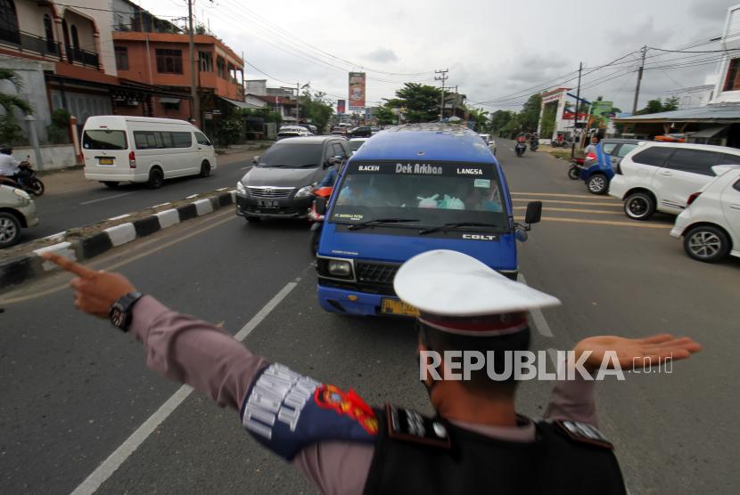 Petugas gabungan Operasi Ketupat mengarahkan mobil angkutan umum untuk putar balik di pos penyekatan mudik (ilustrasi).