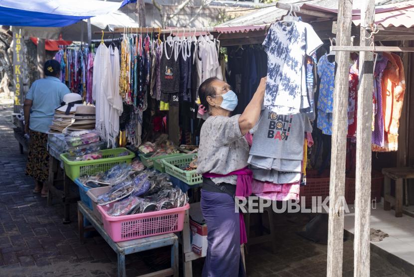 Seorang wanita menunggu pelanggan di luar tokonya di Sanur, Bali, Indonesia, 09 Juni 2021. Pemerintah Indonesia telah merencanakan untuk membuka kembali pulau resor Bali untuk turis asing pada akhir Juli 2021.