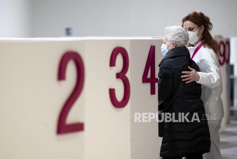 Orang-orang dan petugas kesehatan terlihat selama peresmian pusat baru untuk vaksinasi Covid-19. Ilustrasi.