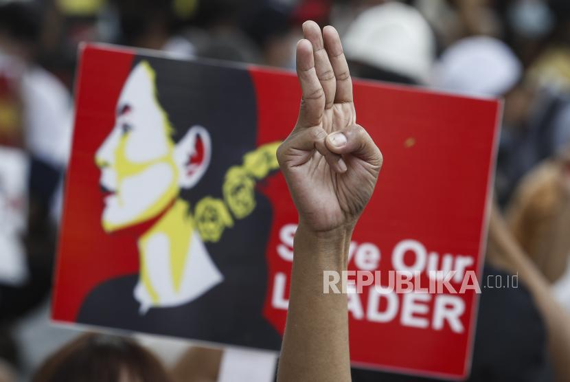 Seorang pengunjuk rasa memberikan hormat tiga jari yang menantang saat yang lain memegang plakat yang menyerukan pembebasan Penasihat Negara Myanmar Aung San Suu Kyi (ilustrasi)