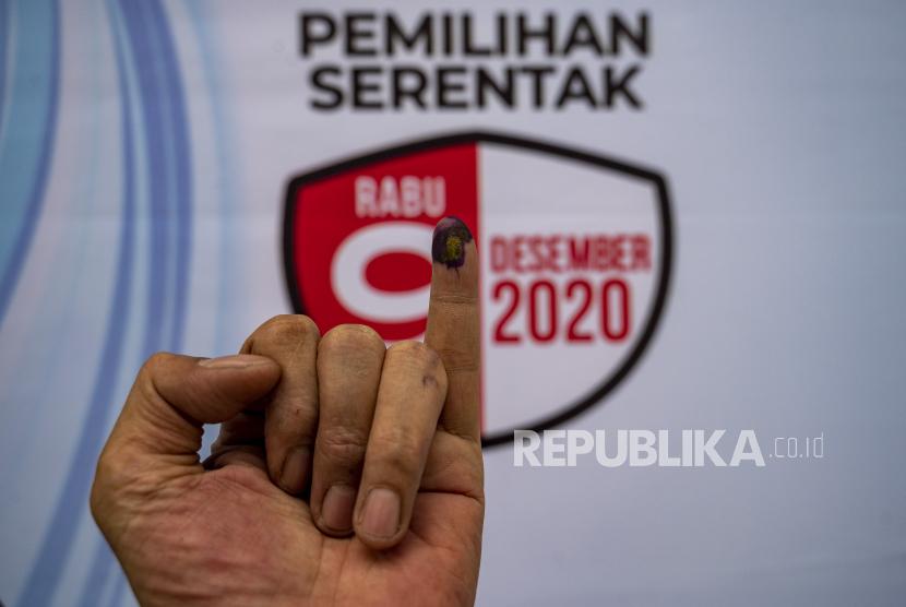 Seorang warga menunjukkan jarinya yang telah ditetesi tinta usai menggunakan hak pilihnya (ilustrasi)