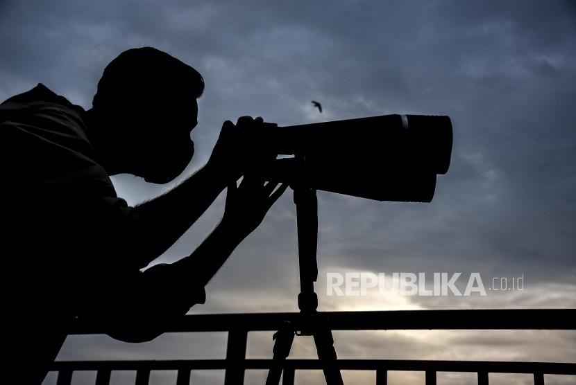 Petugas melakukan pemantauan hilal (rukyatul hilal) menggunakan teleskop di Imah Noong, Lembang, Kabupten Bandung Barat, Senin (12/4). Hasil pemantauan hilal 1 Ramadhan 1442 H di kawasan tersebut tidak tampak karena terhalang cuaca yang berawan
